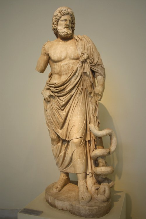 Estátua de Asclépio, cópia romana de um original grego do século 4 a.C., presente no Santuário de Asclépio em Epidauro.  Museu Arqueológico de Atenas. Via Wikimedia Commons.