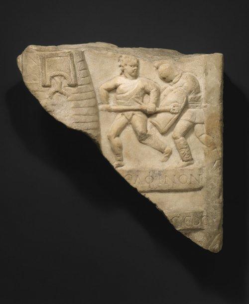Fragmento de relevo em mármore com gladiadores e inscrição em grego. Século 1-3 d.C. MET. N° 57.11.7