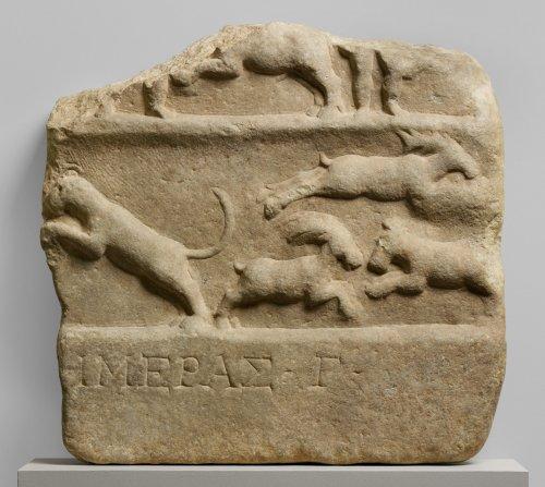 Fragmento mostrando cena de venatio e inscrição em grego. Século 1-2 d.C. MET. N° 26.199.63