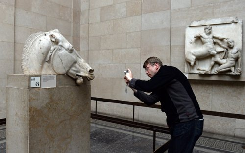 Turista tira fotos de estátua do Partenon no Museu Britânico.